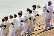 """05 FEBRUARY 2013 - PHNOM PENH, CAMBODIA:  Members of the Royal Court carry King-Father Norodom Sihanouk's ashes to the barge that will carry them up the Mekong River to be scattered. Sihanouk's ashes will be scattered in locations across Cambodia. Tuesday, they were scattered on the Mekong River. Norodom Sihanouk (31 October 1922- 15 October 2012) was the King of Cambodia from 1941 to 1955 and again from 1993 to 2004. He was the effective ruler of Cambodia from 1953 to 1970. After his second abdication in 2004, he was given the honorific of """"The King-Father of Cambodia."""" Sihanouk died in Beijing, China, where he was receiving medical care, on Oct. 15, 2012.   PHOTO BY JACK KURTZ"""