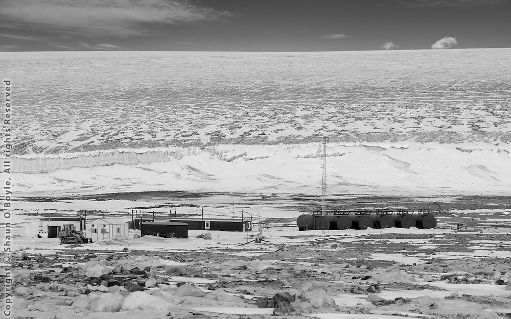 Marble Point station facilities, which are now used primarily as a refueling station for helicopters operating in the McMurdo Dry Valley region. The station is dwarfed by the massive Wilson Piedmont Glacier.