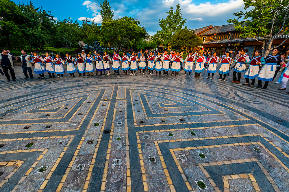 Elderly women of the Naxi ethnic minority group dancing in a square in the Old Town (Dayan) of Lijiang, Yunnan Province, China. The Old Town is a UNESCO World Heritage Site.