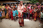 A widow, Rubi Begum, 40 (standing in center), poses for a portrait in Ghagoa Villlage, Gobindagonj Upazila, Gaibandha, Bangladesh on 19th September 2011. Living alone after her husband's passing, she has now (since 2.5 years) found financial independence by working as a saleswoman, earning 3500 - 5000 Bangladeshi Taka per month. She is one of many rural Bangladeshi women trained by NGO CARE Bangladesh as part of their project on empowering women in this traditionally patriarchal society. Named 'Aparajitas', which means 'women who never accept defeat', these women are trained to sell products in their villages and others around them from door-to-door, bringing global products from brands such as BATA, Unilever and GDFL to the most remote of villages, and bringing social and financial empowerment to themselves.  Photo by Suzanne Lee for The Guardian