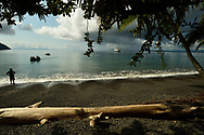 Tourists ride a small inflatable boat into the black sand shoreline of Golfo Dulce, Puntarenas, Costa Rica.