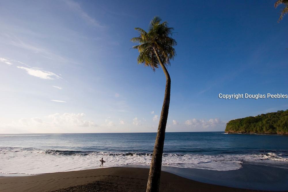 Surfer, Mataiva Bay, black sand beach, Island of Tahiti, French Polynesia<br />