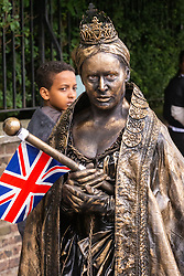"""Queen Victoria"" gets a nervous glance from a child as crowds flock to Lords Cricket Ground, the Home of Cricket to watch the ICC Cricket World Cup final between England and New Zealand. London, July 14 2019."