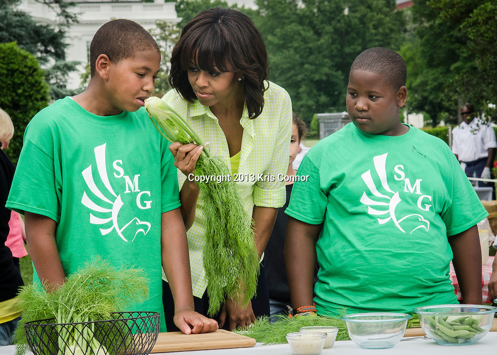 Jordan Wilson(L) and Jalen Hurston(2nd-R) and of Sarah Moore Greene Magnet Technology Academy School, Knox County, TN  with the First Lady Michelle Obama(C) prep vegetables to makes a pizza after harvesting the White House Kitchen Garden for the fifth year in a row at the White House on May 28, 2013 in Washington DC. Photo by Kris Connor