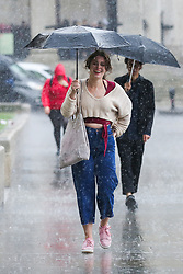 © Licensed to London News Pictures. 27/09/2019. London, UK. A woman shelter from the rain beneath an umbrella during heavy downpour in London. According to the Met Office, this weekend is set to be washout with over 2o hours of rainfall in the capital. Photo credit: Dinendra Haria/LNP. Photo credit: Dinendra Haria/LNP