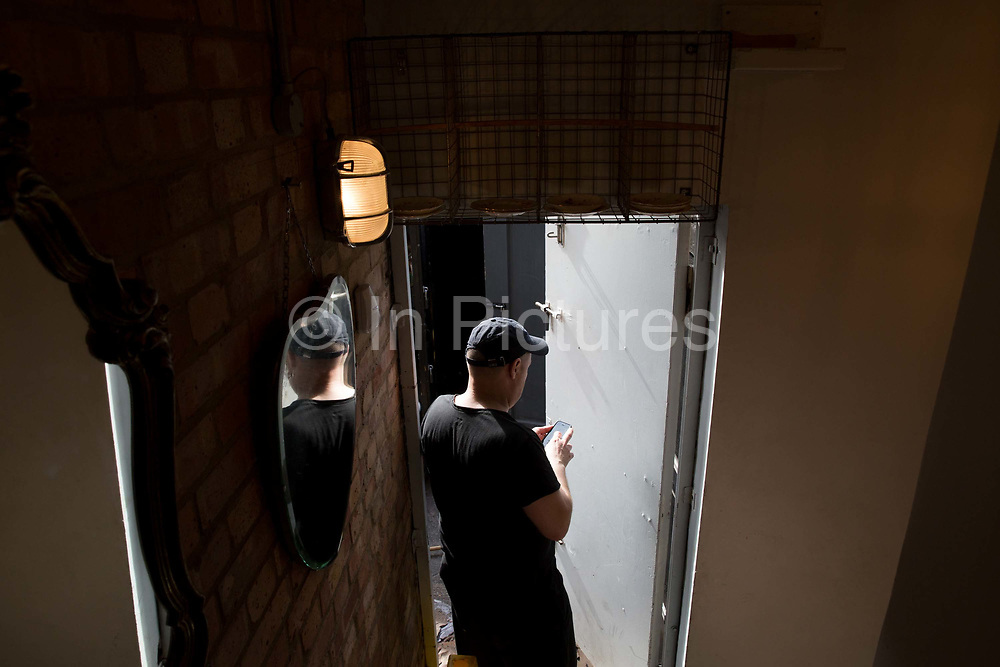 A man checks his mobile phone in a stairwell doorway of a cafe on Broadway Market on 27th May 2017 in London, United Kingdom. Broadway Market is an east London street running from London Fields to the Regents Canal in the London Borough of Hackney. From the series Our Small World, an observation of our mobile phone obsessions
