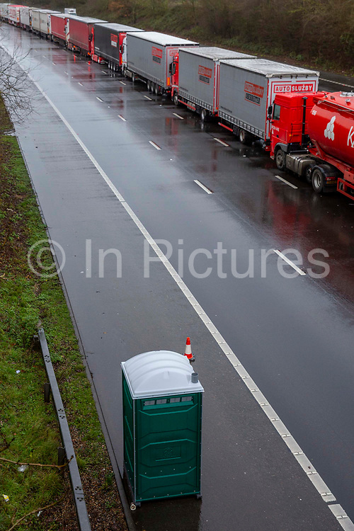 A green mobile toilet for truck drivers as freight lorries line up in queues contained in Operation Stack on the M20 motorway at Ashford, Kent, United Kingdom on the 23rd of December 2020. Truck drivers have been waiting in operation stack on the M20 motorway for over 48 hours now, France closed it's boarders with the UK after a new faster spreading strain of the COVID-19 virus broke out in Kent.