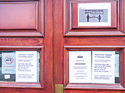Coronavirus Covid-19 social distancing notices on door of Royal Mail delivery office, Woodbridge, Suffolk, England, UK