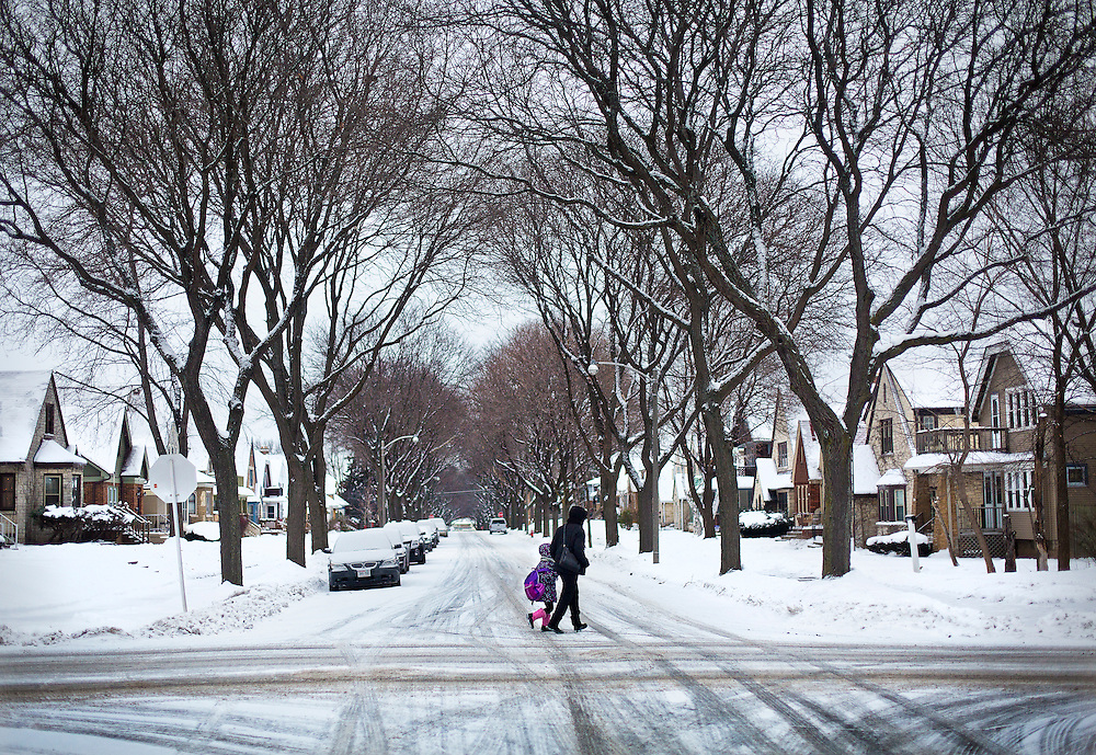 MILWAUKEE, WI – DECEMBER 16: A woman and child cross the street on the 3200 block of N. 44th Street in Milwaukee on Friday, December 16, 2016, the street where Sylville Smith was shot by Milwaukee Police officer Dominique Heaggan-Brown on August 13.