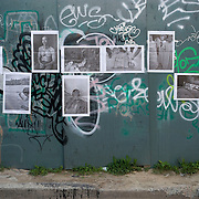 """""""Mira Mexico"""", newspaper exhibition installed on a wall in Toronto, Canada in an alley east of Bathurst St. and South of Queen St. June 3, 2013.<br /> (Credit Image: © Louie Palu)<br /> <br /> Curator<br /> Louie Palu (Canada/USA)<br /> <br /> Using photographs taken by Louie Palu relating to the Mexican drug war, this project challenges the reader to take apart this newspaper to see the full photographs and view the content. The goal is to force the reader to dismantle the vehicle used to deliver news and facts and thereby empower the reader to begin to think more critically. There are 16 photos in total, eight that do not relate to violence and eight that focus on violence or the drug business.. Each photograph is printed on a single sheet of newsprint, so if you take the newspaper apart each sheet of paper will have only one photograph on each side. Only eight pictures can be viewed at one time No photo can be entirely seen unless the reader opens and takes the newspaper apart. <br /> <br /> Once the newspaper comes apart it can be put back together in any order the reader wishes. The page spreads can also be hung as an exhibition. With violent images on one side and non-violent images on the other, the reader must become editor, curator or even censor, choosing how many violent photos are seen vs. how many non-violent photographs are seen. This forces the reader to face up to the fact that all delivery of news involves choices, of what to show and tell and what not to show and tell. It also forces the reader to face up to the system of institutions that serves as the gatekeepers in journalism and the visual arts. The questions are obvious. Is the editor censoring? Is the edit a true depiction of the news and the issue? Are violent images being used effectively to tell a story, or to sensationalize the story? The actual newspaper as an object forces the reader to engage in a a multidimensional exercise in journalism, art, and the politics of representation and me"""
