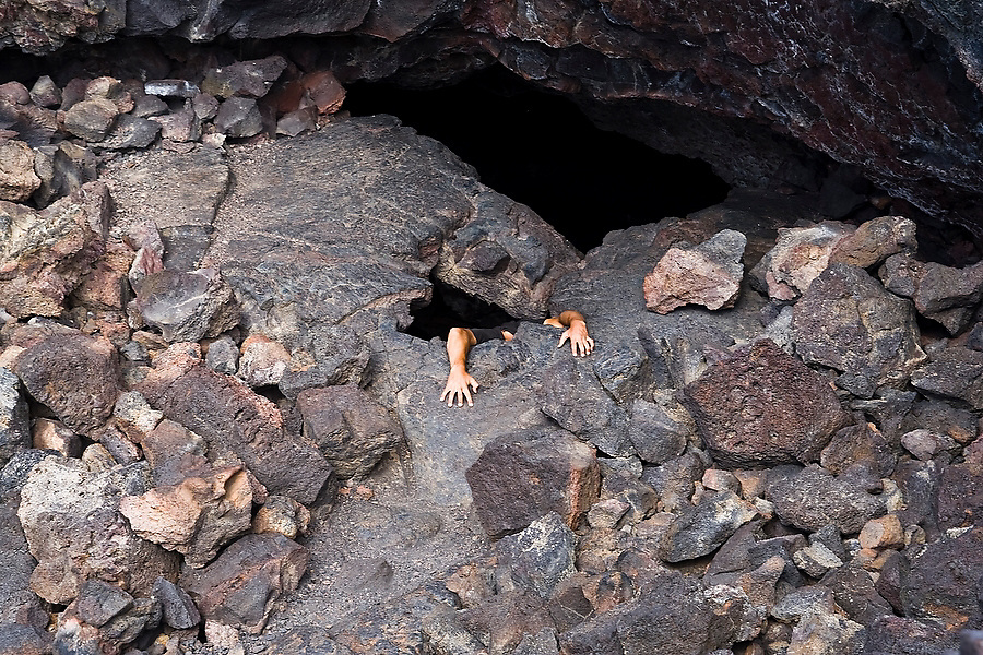 A man, with his head hidden, reaches his arms out of a hole as he climbs out of the giant Indian Tunnel  lava tube in Craters of the Moon National Monument, Idaho.