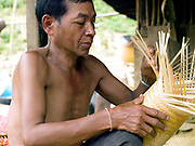 A Khmu man weaving a bamboo sticky rice basket outside his home in Ban Phatao, Phongsaly province, Lao PDR. Renowned for their superior basket weaving skills, the Khmu belong to the Mon-Khmer language group considered to be the original inhabitants of Laos and are the largest ethnic minority with many sub-groups resident in all provinces of Northern Laos. Ban Phatao will soon be temporarily relocated away from the Nam Ou river due to the construction of the Nam Ou Cascade Hydropower Project Dam 5.