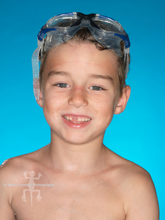 Wet, 7 year old boy smiles with swim goggles and missing front tooth.