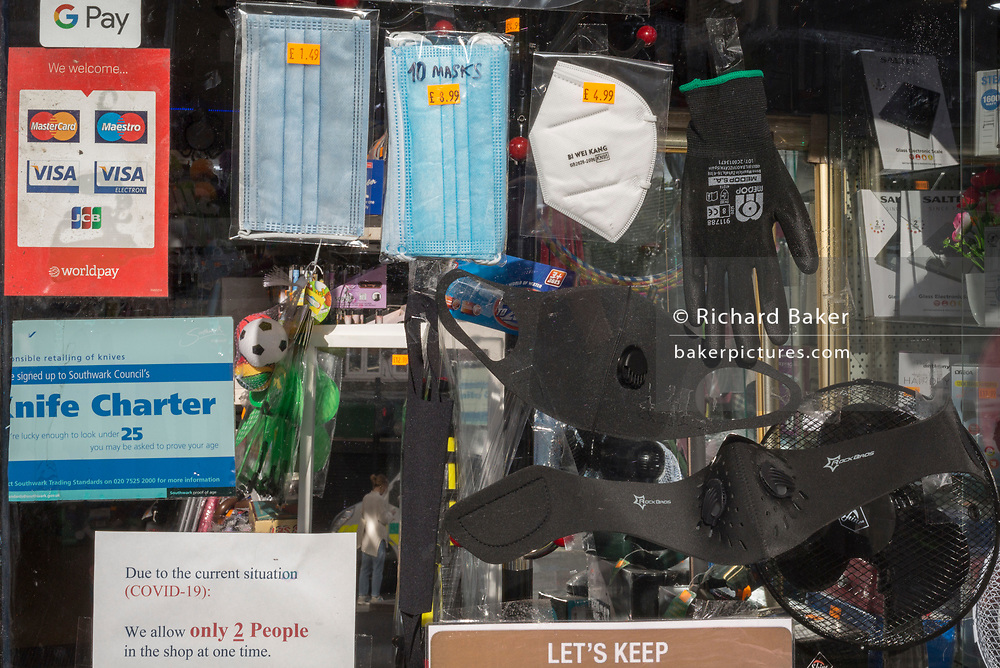 The day after UK Prime Minister Boris Johnson addressed the nation with his roadmap for the coming weeks and months during the Coronavirus pandemic lockdown, and asking the British public to wear face masks when travelling on the transport system, various masks and gloves are on sale in the window of a hardware shop in Camberwell, on 11th May 2020, in London, England.