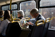 Listening to an mp3 device, a man reads the Sports section of his newspaper on the top deck of a London bus.