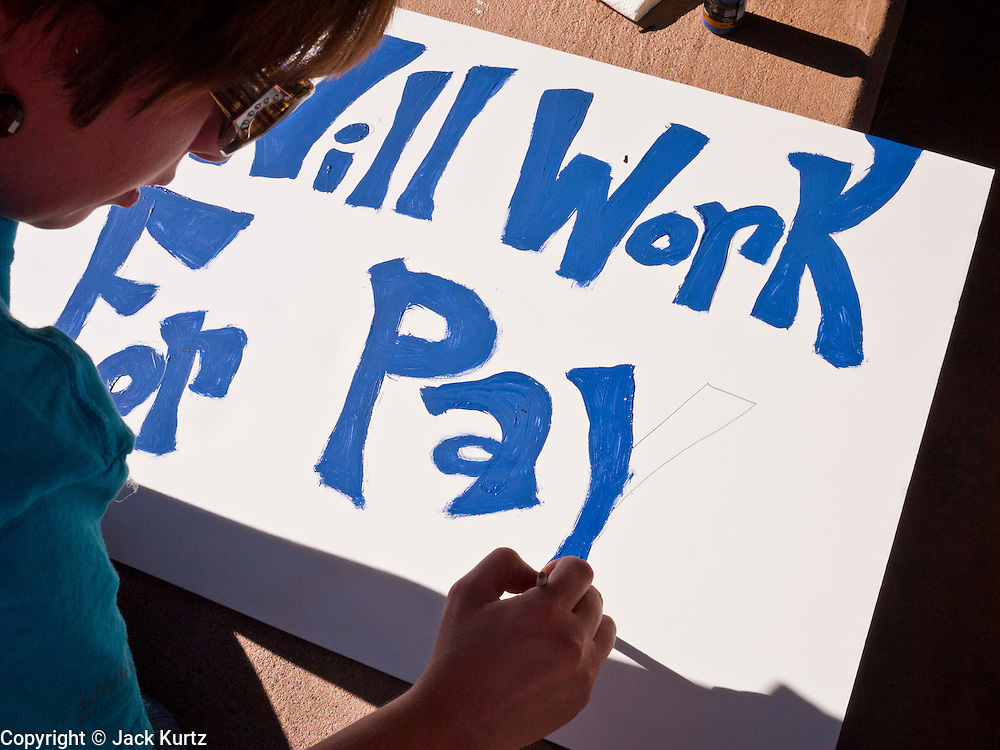 """09 OCTOBER 2011 - PHOENIX, AZ: KRYSTAL paints a sign that reads """"Will Work for Pay"""" during an Occupy Phoenix sign painting party Sunday. About 50 people met in Steele Indian School Park in central Phoenix to paint signs for the Occupy Phoenix demonstration, which is expected to take place on Oct 15. Organizers are expecting more than 1,000 people to come downtown Saturday to protest against big banks and high unemployment.    PHOTO BY JACK KURTZ"""