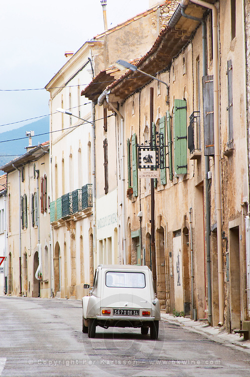 Domaine d'Aupilhac. Montpeyroux. Languedoc. The winery building. An old Citroen 2 CV car driving on the street. France. Europe.