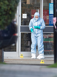 © Licensed to London News Pictures. 03/02/2020. London, UK. A police scenes of crime officer looks at evidence markers placed on the ground outside Boots where the assailant was shot in Streatham High Road the day after he stabbed two people. Sudesh Amman, who was released from prison recently for terror offences, was under active police surveillance at the time of the attack - which police think was an Islamist-related terrorist incident. Photo credit: Peter Macdiarmid/LNP