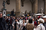 An Asian tour group admires renaissance statues in Florence's Loggia dei Lanzi, Piazza della Signoria...The Loggia dei Lanzi, also called the Loggia della Signoria, is a building on a corner of the Piazza della Signoria in Florence, Italy, adjoining the Uffizi Gallery. It consists of wide arches open to the street, three bays wide and one bay deep. The arches rest on clustered pilasters with Corinthian capitals. Rape of the Sabine Women by the Flemish artist Jean de Boulogne, better known by his Italianized name Giambologna