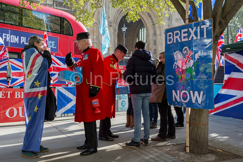 On the day that the EU in Brussels agreed in principle to extend Brexit until 31st January 2020 aka Flextension and not 31st October 2019, two Chelsea Pensioners sell Remembrance poppies, next to Brexit Party flags and banners during a Brexit protest outside parliament, on 28th October 2019, in Westminster, London, England.