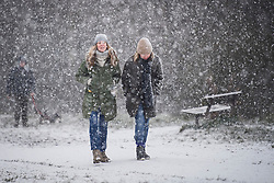 © Licensed to London News Pictures. 24/01/2021. London, UK. Two women walk through heavy Snowfall on Hampstead Heath in Hampstead in north London. Parts of the UK continue to suffer from flooding caused by Storm Christoph. Photo credit: Ben Cawthra/LNP
