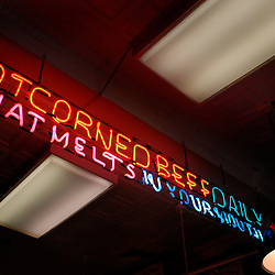 """A neon sign in Attman's New York Delicatessen bears the slogan """"Hot Corned Beef Daily that Melts in Your Mouth.""""..Photo by Susana Raab"""