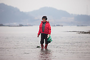 """Women standing on the slowly closing """"Mysterious Sea Road"""" in Hoedong shore (Jindo island). Jindo is the 3rd biggest island in South Korea located in the South-West end of the country and famous for the """"Mysterious Sea Route"""" or """"Moses Miracle"""". Every spring thousands flock to the shores of Jindo to walk the mysterious route that stretches roughly three kilometers from Hoedong to the distant island of Modo. Materializing from the rise and fall of the tides, the divide can reach as wide as forty meters."""