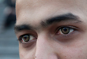 Young Asian male wearing coloured contact lenses. Scene outside as people flock away from the old Stratford shopping centre towards the new Westfield Shoppping Centre in Stratford, East London, UK. This is Europe's largest shopping complex. This is a relatively poor area of London, but in recent years has seen much regeneration, the construction of a major transport hub and various shopping complexes. Stratford is adjacent to the London Olympic Park and is currently experiencing regeneration and expansion linked to the 2012 Summer Olympics.