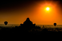 Silhouette Morning: Under the brilliance of a golden morning, balloons slowly drift in silhouette past a gigantic Buddhist Temple, Bagan Myanmar.