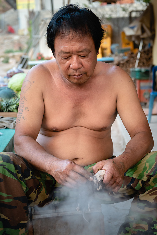 Portrait of a man cooking and skinning a rat in Pak Beng, Laos