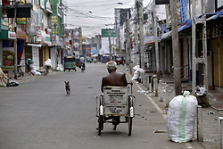 October 13, 2017 - Jaffna, Sri Lanka - An elderly handicapped man rides his wheelchair on a deserted street in Jaffna city in the Norther province of Sri Lanka on 13 Friday October 2017...Most shops were seen closed due to a 'Hartal'  as a mark of protest demanding the release of Tamil political prisoners. (Credit Image: © Tharaka Basnayaka/NurPhoto via ZUMA Press)