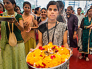 07 SEPTEMBER 2014 - BANGKOK, THAILAND: A woman receives blessings during the Ganesh Festival at Central World in Bangkok. Ganesh Chaturthi, also known as Vinayaka Chaturthi, is a Hindu festival dedicated to Lord Ganesh. It is a 10-day festival marking the birthday of Ganesh, who is widely worshiped for his auspicious beginnings. Ganesh is the patron of arts and sciences, the deity of intellect and wisdom -- identified by his elephant head. The holiday is celebrated for 10 days, in 2014, most Hindu temples will submerge their Ganesh shrines and deities on September 7.     PHOTO BY JACK KURTZ