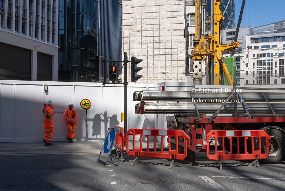 Construction traffic marshals stand against a hoarding surrounding a new project on Fenchurch Street in the City of London, the capital's financial district, on 29th July 2020, in London, England.