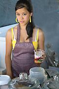 Teenage food worker serving an interesting cup of Hmong cuisine. Hmong Sports Festival McMurray Field St Paul Minnesota USA