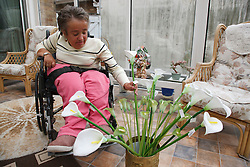 Wheelchair user with Spina Bifida arranging flowers in her conservatory.