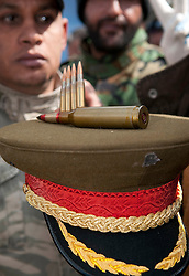 © under license to London News Pictures. 25/02/2011. Men show off bullets atop a classic Gaddafi military hat. Photo credit should read Michael Graae/London News Pictures