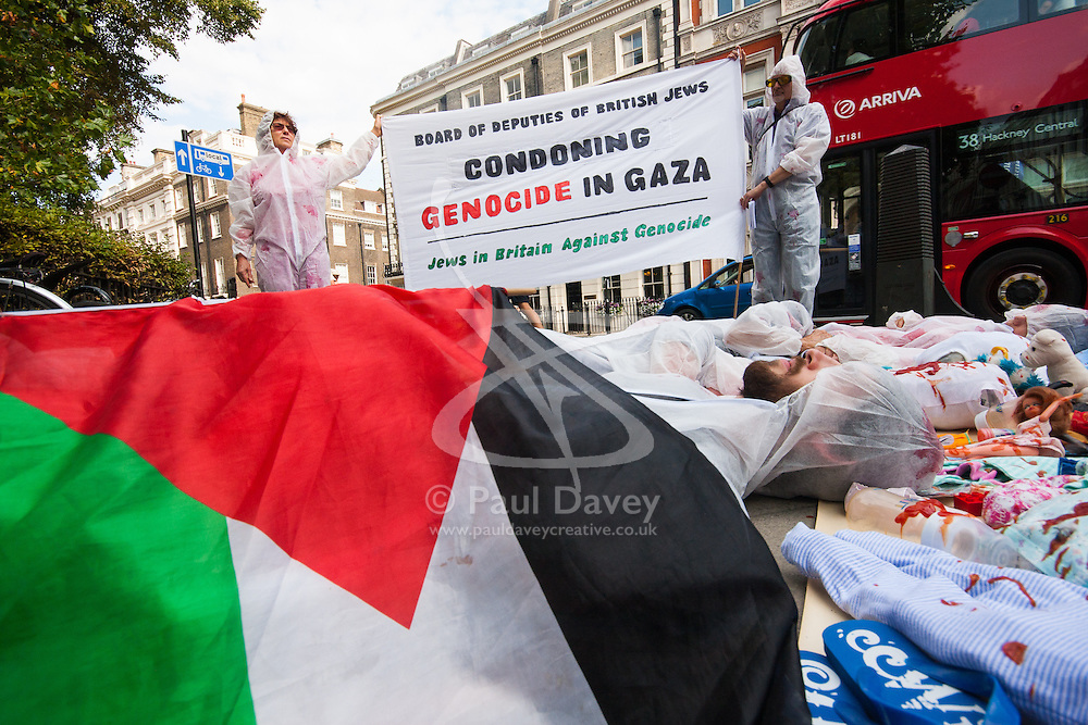 """London, August 4th 2014. Protesters from British Jews Against Genocide lie on the ground surrounded by """"blood"""" spattered children's toys and headless dolls symbolising the over 400 children killed in Gaza since Israel's Operation Protective Edge began.continue."""