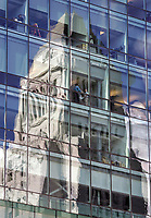 4/28/05-LOS ANGELES- Two men stand in a window of the new California Department of Transportation building on 1st Street in downtown Los Angeles. Los Angeles City Hall is reflected in the windows of the building. David Sprague/Daily News