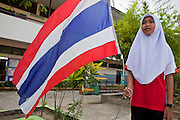 """Sept. 27, 2009 -- PATTANI, THAILAND: A Muslim girl holds the Thai flag before classes at the Gahong School in Pattani, Thailand, Sept 27. Schools and school teachers have been frequent targets of Muslim insurgents in southern Thailand and the army now provides security at many government schools.  Thailand's three southern most provinces; Yala, Pattani and Narathiwat are often called """"restive"""" and a decades long Muslim insurgency has gained traction recently. Nearly 4,000 people have been killed since 2004. The three southern provinces are under emergency control and there are more than 60,000 Thai military, police and paramilitary militia forces trying to keep the peace battling insurgents who favor car bombs and assassination.  Photo by Jack Kurtz / ZUMA Press"""