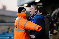 An angry Millwall fan having to be restrained by a steward after watching his side concede another goal<br /> <br /> Photographer Craig Mercer/CameraSport<br /> <br /> Football - The Football League Sky Bet Championship - Millwall v Middlesbrough - Saturday 6th December 2014 - The Den - London<br /> <br /> © CameraSport - 43 Linden Ave. Countesthorpe. Leicester. England. LE8 5PG - Tel: +44 (0) 116 277 4147 - admin@camerasport.com - www.camerasport.com
