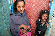 Afghanistan. Two girls, sisters, Ferisha aged 11 and Zahla Bibi aged 6, stand in a doorway. Charahi Spinkali, district 5, Kabul .