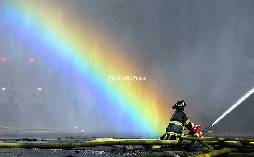 A ray of sunlight creates a rainbow in the mist of water coming from Seattle firefighters who worked to control the blaze at an abandoned building in Seattle. (John Lok / The Seattle Times)