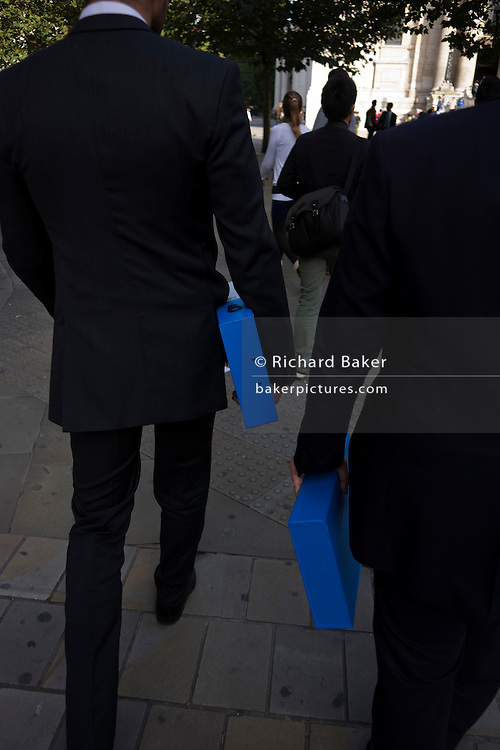 Two businessmen in dark formal suits carry identical blue boxes along a London street. Walking away with their backs to us, the two men stride towards an appointment in the City of London. The two boxes are both held in the arms of both executives as they cross the churchyard in front of St. Paul's cathedral in the capital's financial district.