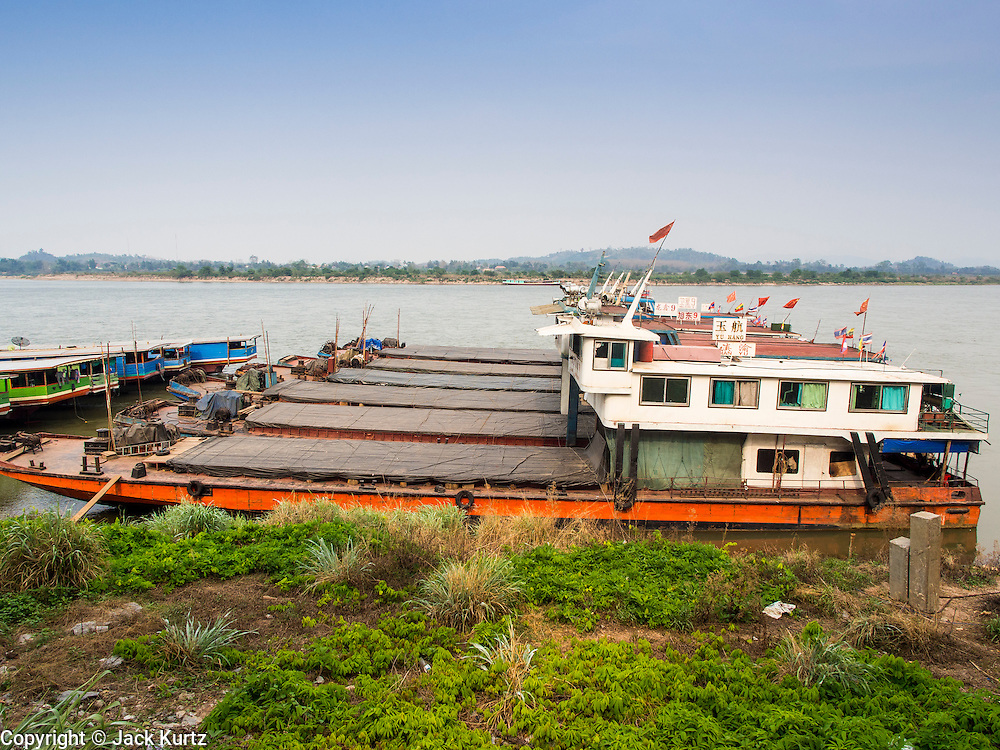 21 APRIL 2014 - CHIANG SAEN, CHIANG RAI, THAILAND: Chinese flagged river boats tied up in the port in Chiang Saen, Thailand. Chiang Rai province in northern Thailand is facing a drought this year. The 2014 drought has been brought on by lower than normal dry season rains. At the same time, closing dams in Yunnan province of China has caused the level of the Mekong River to drop suddenly exposing rocks and sandbars in the normally navigable Mekong River. Changes in the Mekong's levels means commercial shipping can't progress past Chiang Saen. Dozens of ships are tied up in the port area along the city's waterfront.      PHOTO BY JACK KURTZ
