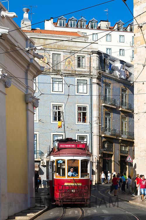 Tourist tram on a tour through harrow steep streets of Alfama District of Lisbon, Portugal