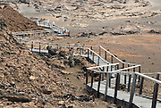 A boardwalk protects a lava landscape from erosion on the summit of Bartolomé Island (or Bartholomew Island, named after Lieutenant David Bartholomew of the British Navy), one of the geologically younger islands in the Galápagos archipelago, just off the east coast of Santiago (James) Island. The volcanic Galápagos Islands (officially Archipiélago de Colón, otherwise called Islas de Colón, Islas Galápagos, or Enchanted Islands) are distributed along the equator in the Pacific Ocean 972 km west of continental Ecuador, South America. In 1959, Ecuador declared 97% of the land area of the Galápagos Islands to be Galápagos National Park, which UNESCO registered as a World Heritage Site in 1978. Ecuador created the Galápagos Marine Reserve in 1998, which UNESCO appended in 2001.