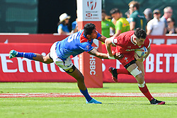 Joe Goodchild of Wales evades the tackle of Belgium Tuatagaloa of Samoa <br /> <br /> Photographer Craig Thomas/Replay Images<br /> <br /> World Rugby HSBC World Sevens Series - Day 2 - Friday 6rd December 2019 - Sevens Stadium - Dubai<br /> <br /> World Copyright © Replay Images . All rights reserved. info@replayimages.co.uk - http://replayimages.co.uk