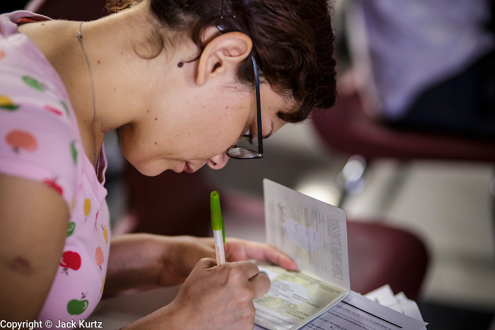 """25 AUGUST 2012 - PHOENIX, AZ: A woman copies information from her passport while she completes the deferred action paperwork Saturday. Hundreds of people lined up at Central High School in Phoenix to complete their paperwork to apply for """"Deferred Action"""" status under the Deferred Action for Childhood Arrivals (DACA) program announced by President Obama in June. Volunteers and lawyers specialized in immigration law helped the immigrants complete the required paperwork. Under the program, the children of undocumented immigrants brought to the US before they turned 16 years old would not be subject to deportation if they meet a predetermined set of conditions.     PHOTO BY JACK KURTZ"""