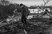 Young refugee trying to salvage belongings after half of the camp was destroyed by fire. The Jungle. Migrant Camp, Calais, France. 2016