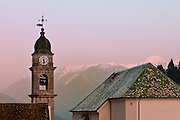 Gothic style clock tower of church in Pesariis,  with snow capped mountain in background